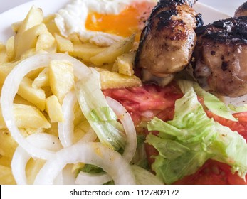 combinated dish with chicken legs, french fries, fried egg and salad