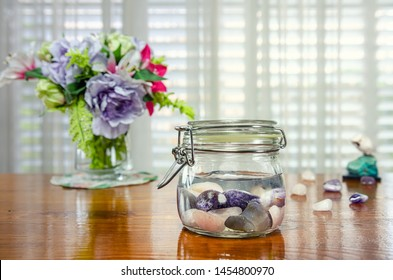 Combination of amethyst, rose quartz and blue lace agate making gem elixir in a glass jar on a table. Stones create highly vibrational water that captures the gemstone meanings and healing properties.