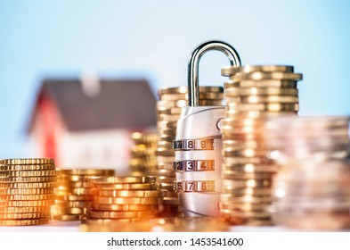 Combination lock with several stacks of coins and house in the background