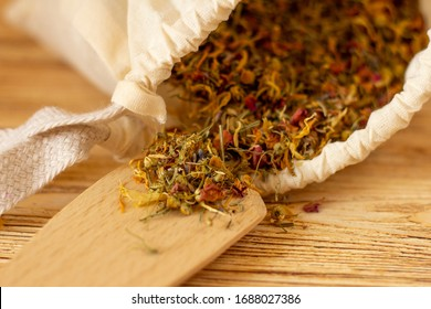 Combination of useful aromatic herbs for tea, bath, cosmetics, picking herbs of healing calendula, anti-inflammatory chamomile, fragrant rose, calming lavender in white cotton bag with wooden spatula