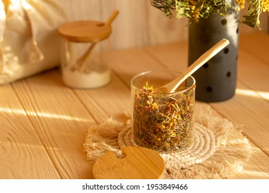 Combination of useful aromatic herbs for tea, bath, cosmetics, picking herbs of healing calendula, anti-inflammatory chamomile, fragrant rose, calming lavender in glassful with wooden spoon