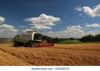 Combine in barley field, summer harvest, blue sky with clouds, side perspective