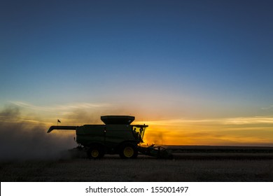 A combine during the fall harvest at sunset on the prairies