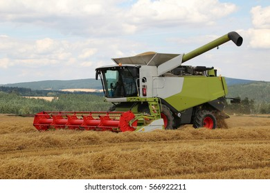 Combine with full tank of barley during hot summer day with blue cloudy sky on background, bio agriculture, frontal perspective, waiting to empty grain container, straw in lines