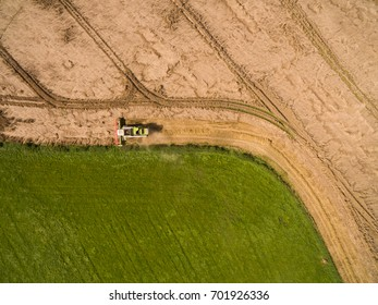 combine harvester - aerial view of modern combine harvester at the harvesting the wheat on the golden wheat field in the summer - Cereal harvest