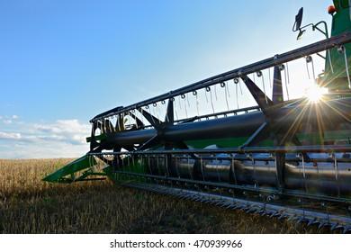 Combine Harvester in Barley Field during Harvest backlit by sun