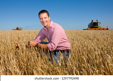 Combine harvester harvesting field with farmer inspecting barley crop