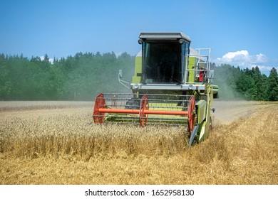 Der Erntemaschentrieb erntet vor einem Wald ein kleines, reifes Weizenfeld