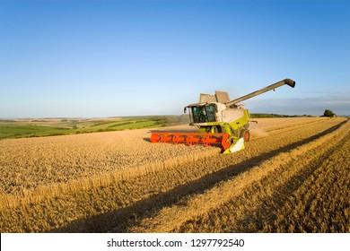 Combine harvester harvesting wheat field on farm against blue sky