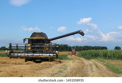 Combine harvester and a small red tractor on behind in a countryside scenery during agricultural activity