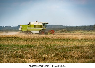 combine harvester that is harvesting wheat with dust straw in the air