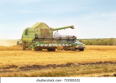 Combine harvester and truck in field