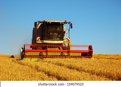 Combine harvester at work harvesting a field of wheat