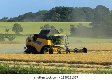 Combine Harvester Working At Harvest Time On Cotswold Farmland. England. UK