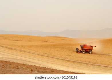 Combine harvesting crops on Palouse Hills in Washington state