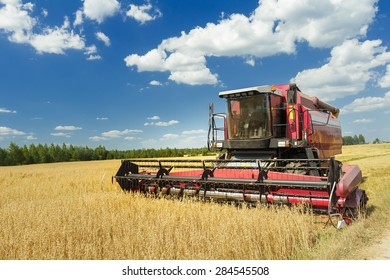 Combine machine with air-conditioned cab is harvesting oats on farm field