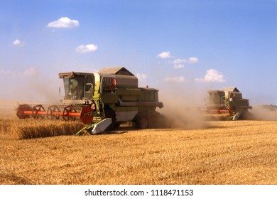 combines harvesting on ripe corn flield on sunny day