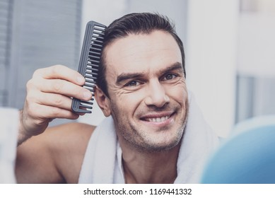 Combing. Handsome joyful model expressing cheerful emotions while looking at you and combing his hair