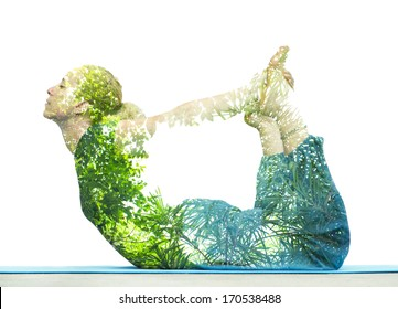 Combining nature with spiritual yoga in a creative portrait of a young woman lying with her body arched holding her toes and her eyes closed in serenity, superimposed with the foliage of trees