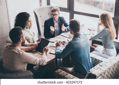 Combining their expertise. Young handsome man in glasses gesturing and discussing something with his coworkers while sitting at the office table