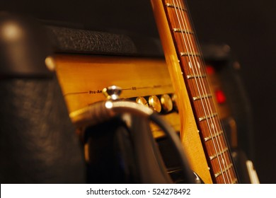 Combo amplifier for guitar with classic electric guitar on the black background. Shallow depth of field, low key, close up.