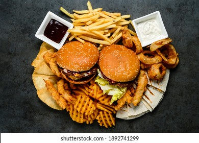 Combo large set of fast food burgers french fries and snacks. Juicy delicious hamburger, French fries, chicken legs and sauce. Served on black background. Fast food restaurant. Food delivery.