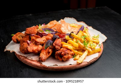 Combo snacks composition with chicken wings, lamb ribs, sausages, fried shrimp, onion rings, nuggets fish and turkeys, squid rings, suluguni with french fries and tartar sauce and BBQ