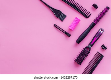 Combs and hairdresser tools in beauty salon work desk on pink background top view mockup