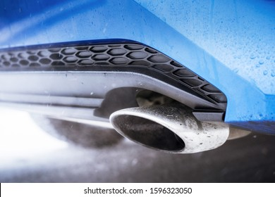 Combustion fumes coming out of car exhaust pipe of blue modern car