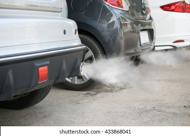 combustion fumes coming out of car exhaust pipe