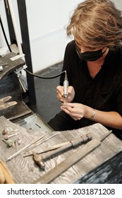 Comcentrated femele jeweler in mask sitting at work station and using abrasive nozzle while creating design of ring