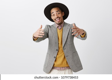 Come closer, let me hug you. Studio shot of positive friendly african-american man in trendy outfit and hat pulling hands towards camera, inviting mates to come inside, welcoming guest to party
