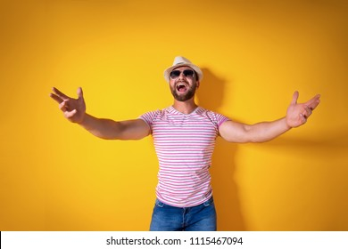 Come closer, let me hug you. Studio shot of positive friendly bearded man in trendy stripped outfit and hat pulling hands towards camera, inviting mates to come inside, welcoming guest to party