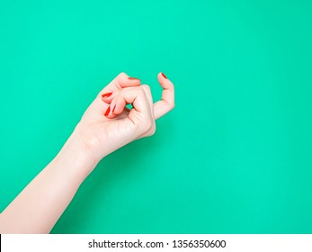 The Come Hither Hand Sign. Woman hand beckoning on isolated turquoise green color background. Female hand beckoning isolated on white background. Woman gesturing with one finger, come here symbol
