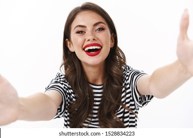 Come to me. Cheerful charming friendly-looking alluring woman reaching to give kiss, stretch hands sideways hold camera, taking selfie photographing in glamour outfit, stand white background