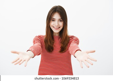 Come to me, want give you warm hug. Portrait of friendly caring sister with happy stunning smile, pulling hands towards camera, inviting friend to cuddle, standing joyfully over gray background