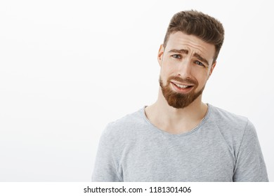 Come on man it is lame. Unimpressed displeased handsome businessman with beard and blue eyes, tilting head and frowning squinting and tightening smile from dissatisfaction and unwillingness