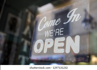 """""""Come in we are open"""" sign board through the glass of store window."""
