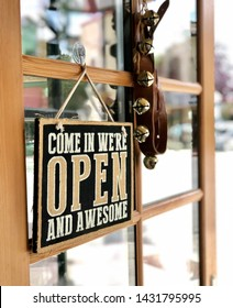Come in we are open sign hanging on the door of a small business. Bells hang on the door to let the store owner know someone has come in