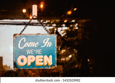 Come In We're Open sign on door of coffee cafe shop.