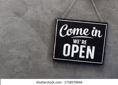 Come in we're open, vintage black retro sign in back wall