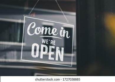 Come in we're open, vintage black retro sign in glass door storefront - Shutterstock ID 1727038885