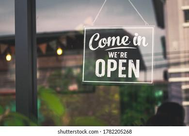 Come in we're open, vintage black retro sign in glass door storefront