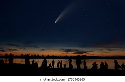 Comet Neowise and crowd of people  silhouetted by the Ottawa river admiring and photographing the comet