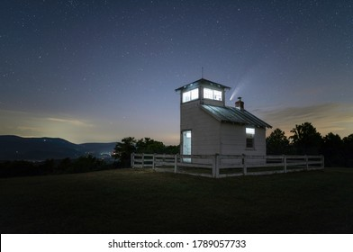 Comet Neowise sets over an illuminated fire watchtower atop a meadow just east of Shenandoah National Park in the Virginia Piedmont region.