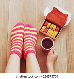 Comfort Concept - Woman drinking hot cocoa and eating delicious macaroon. Close-up of female legs in bright colored warm socks with a retro vintage instagram filter.