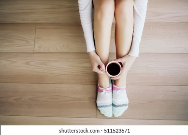 Comfort Concept - Woman drinking hot cocoa and sitting on the floor parquet. Close-up of female legs in bright colored warm socks with a retro vintage instagram filter, top view