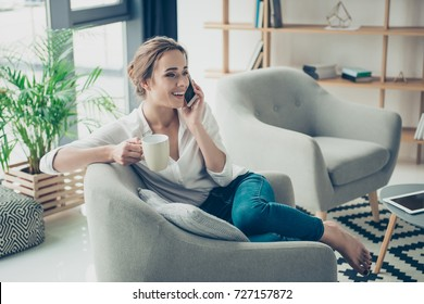 Comfort and cozy girlish time. Cute lady in smart trendy wear is chatting on her telephone, sitting on armchair. Smiling, sitting in relaxing atmosphere indoors at home, with plants and nice design