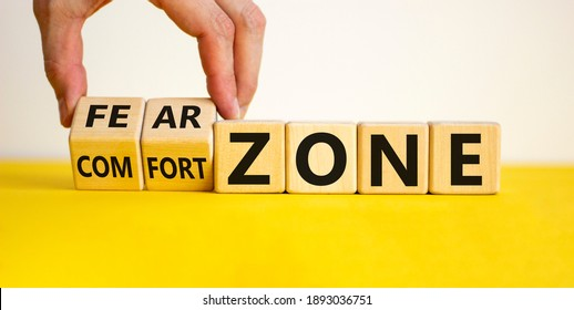 Comfort or fear zone symbol. Hand turns wooden cubes and changes words 'comfort zone' to 'fear zone'. Beautiful yellow table, white background, copy space. Business, psychology concept.
