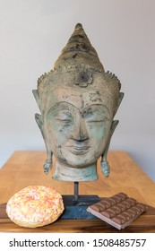 Comfort food. Mental health and wellbeing with spiritual Buddha statue, sweet doughnut and chocolate. Representing mind over desire. Self control in the face of temptation.